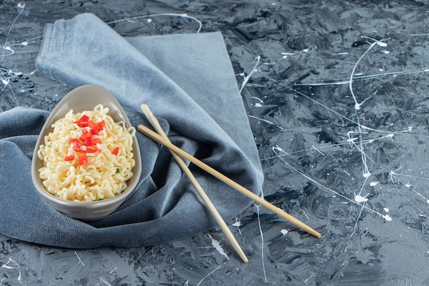 A bowl of noodle next to chopsticks on a pieces of fabric, on the marble background.