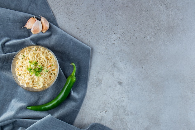 A bowl of noodle, pepper and garlic on a pieces of fabric, on the marble background.