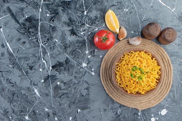Una ciotola di pasta su un sottopentola accanto a pomodori, limone e aglio, sullo sfondo di marmo.