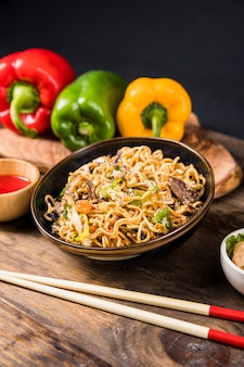 Bowl of noodles with bell peppers and chopstick on wooden desk
