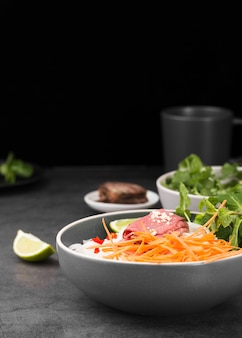 Bowl of noodles with carrots and copy space