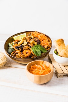 Bowl of noodles with spring roll and grated carrot on wooden table against white backdrop