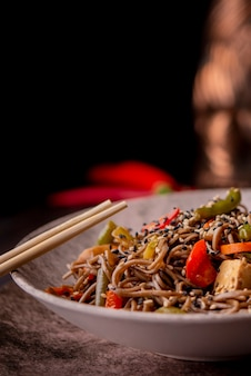 Bowl of noodles with vegetables and copy space