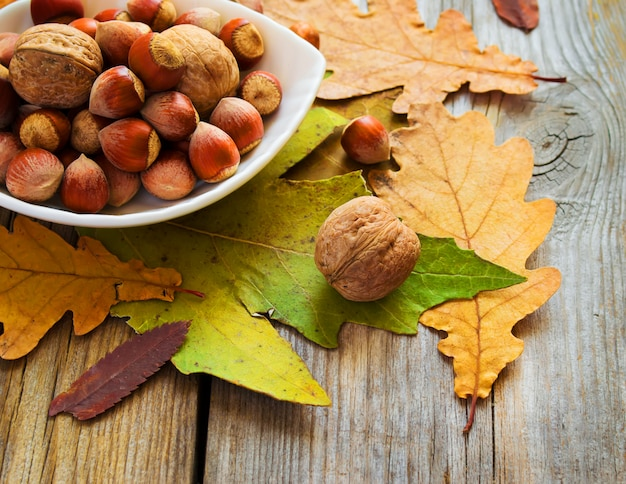 Bowl of nuts and autumn leaves on the old wooden table