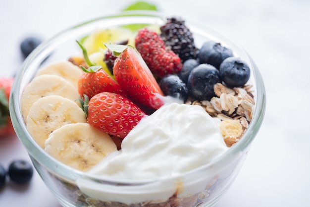 Bowl of oat granola with yogurt, fresh blueberries, mulberry, strawberries, kiwi, banana, mint and nuts board for healthy breakfast, top view, copy space, flat lay. vegetarian food concept.
