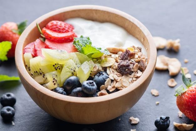 Bowl of oat granola with yogurt, fresh blueberries, strawberries, kiwi mint and nuts board for healthy breakfast,  healthy breakfast menu concept. on the black rock
