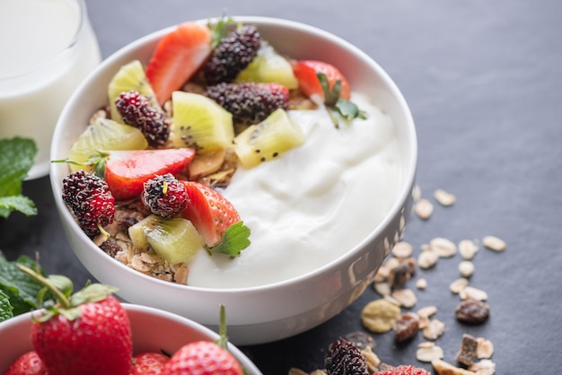 Bowl of oat granola with yogurt, fresh mulberry, strawberries, kiwi mint and nuts on the black rock board for healthy breakfast, copy space. healthy breakfast menu concept.