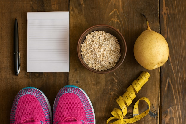 Bowl of oatmeal, banana with yellow tape for measuring figure, empty notepad and trainers on dark wooden background