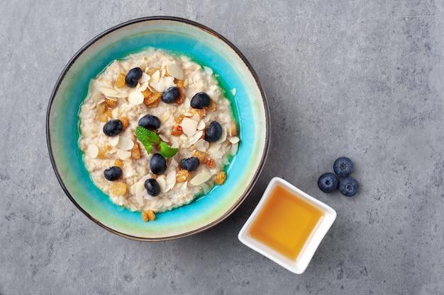 Bowl of oatmeal porridge with almond flakes, blueberries, raisins, and honey