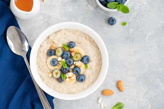 Bowl of oatmeal porridge with banana, blueberries and almonds