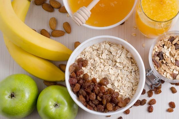 Bowl of oatmeal and raisins. honey, bananas, green apples, nuts