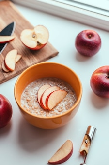 Bowl of oatmeal with apple against white table