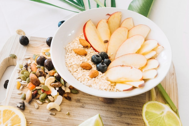 Bowl of oatmeal with apple slice and dryfruits on chopping board