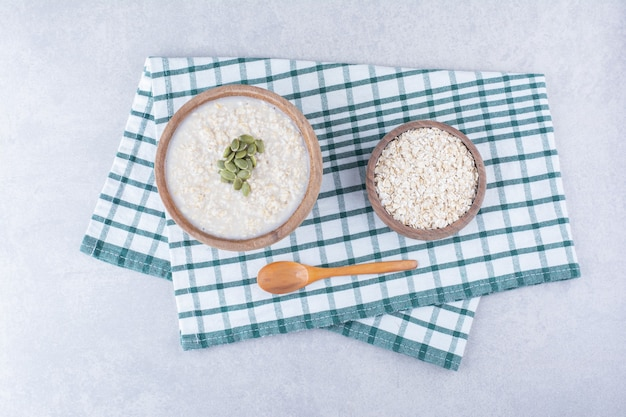 A bowl of oats and a bowl of oatmeal topped with pepitas, next to a spoon on a towel on marble surface