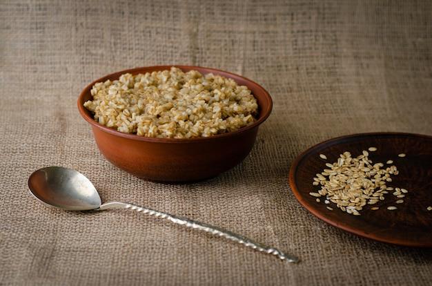 A bowl of oats porridge on sackcloth
