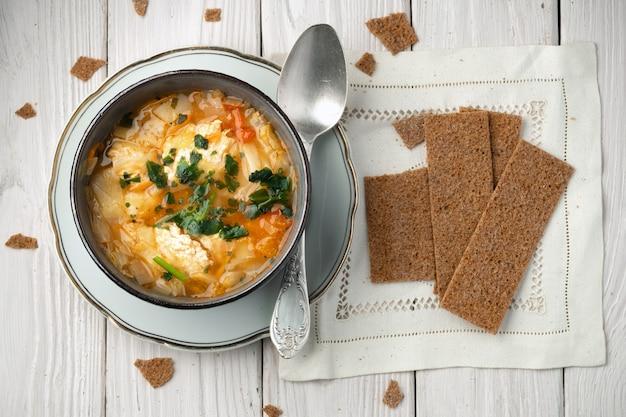 Чаша вкусного горячего супа с куриными тефтелями и ржаными хлебцами на белых деревянных досках