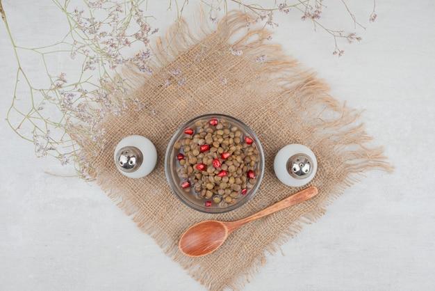 ザクロの種と黄麻布に塩を入れた豆のボウル。
