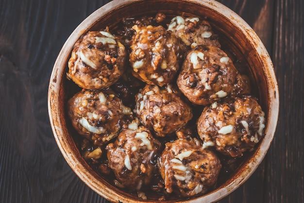 강판 치즈를 곁들인 쇠고기와 돼지 고기 미트볼 그릇
