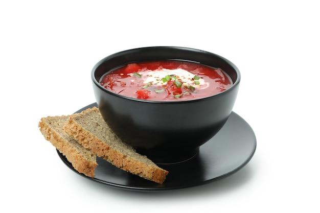 Чаша свекольного супа и ломтики хлеба, изолированные на белой поверхности