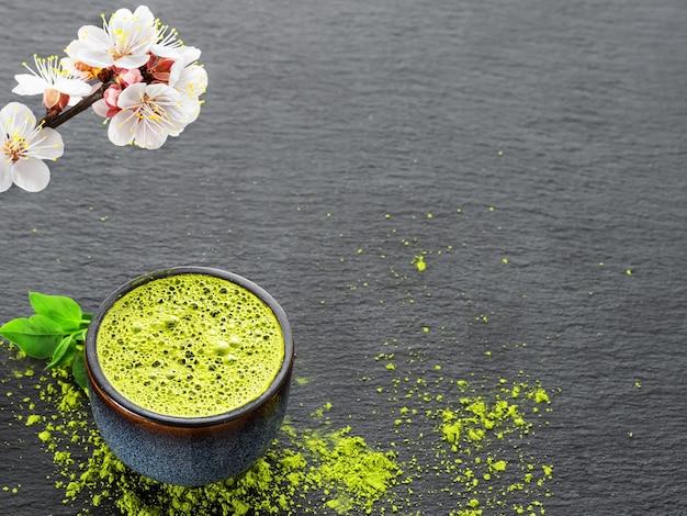 Чаша синего с зеленым чаем матча, рядом с веткой цветущей вишни и чайного порошка на столе
