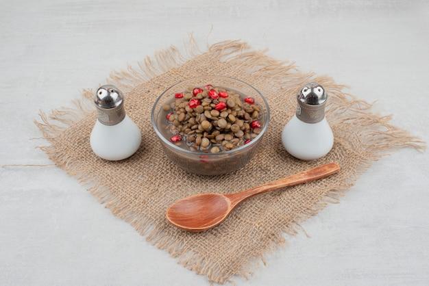 ザクロの種と黄麻布に塩を入れたゆで豆のボウル。