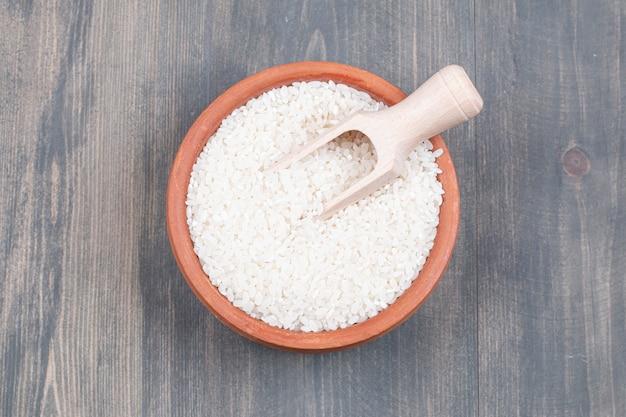 Чаша отварного риса с ложкой на деревянном столе