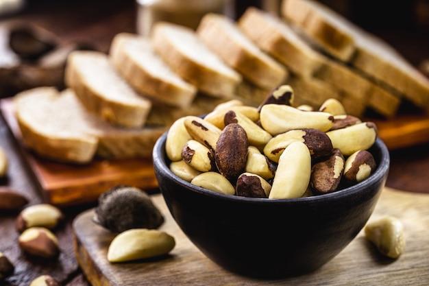 Чаша бразильских орехов с веганским цельнозерновым хлебом на заднем плане, ингредиент для здоровой веганской кухни, экзотический орех