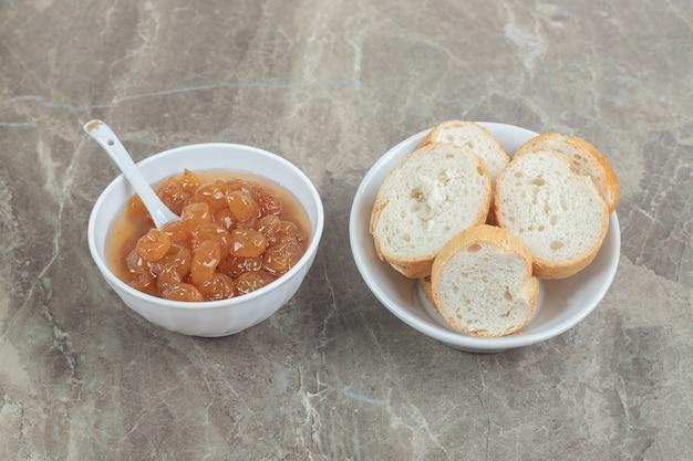 Чаша ломтиков хлеба и ягодного варенья на мраморе. фото высокого качества
