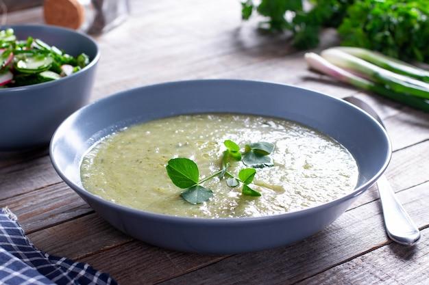 ブロッコリーとグリーンピースのクリームスープのボウル、木製のテーブル、野菜スープ