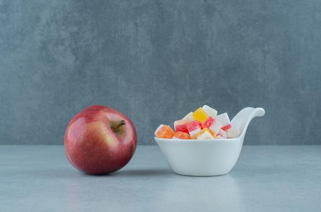 Миска конфет и свежее яблоко на мраморе.