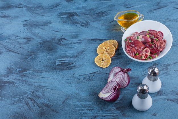 青の背景に鶏内臓、オイルボウル、塩、タマネギ、レモンのボウル。