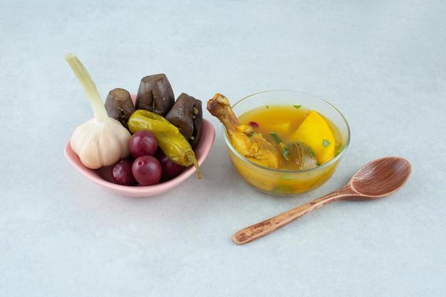 Чаша куриного супа и миска ферментированных овощей.