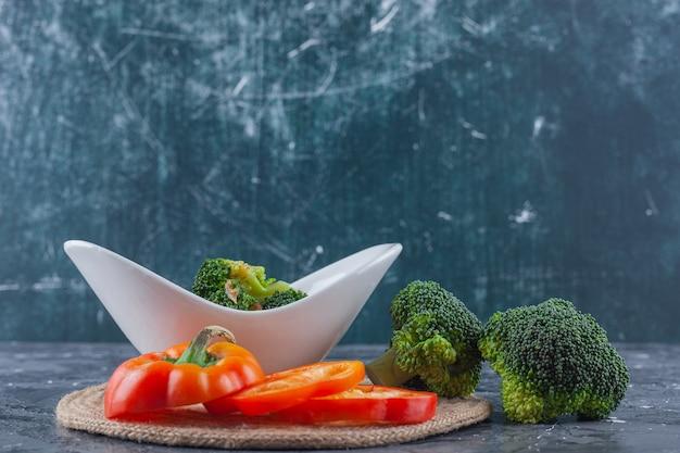 青い表面のトリベットにチキンスープと野菜のボウル