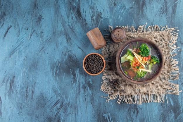 Чаша куриного супа на салфетке из мешковины, на синем фоне.