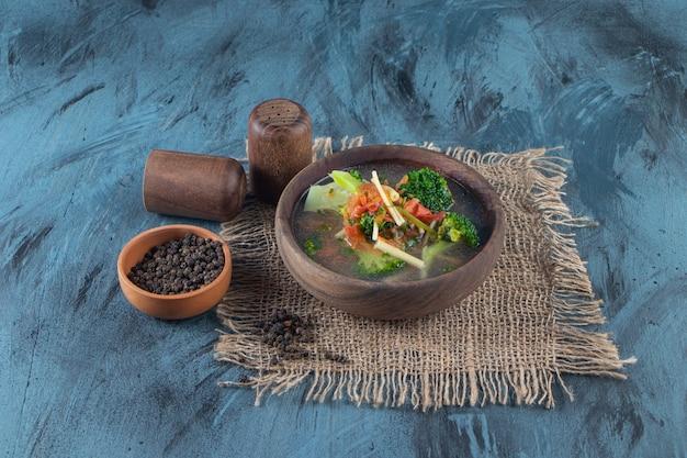 Чаша куриного супа на салфетке из мешковины, на синей поверхности.