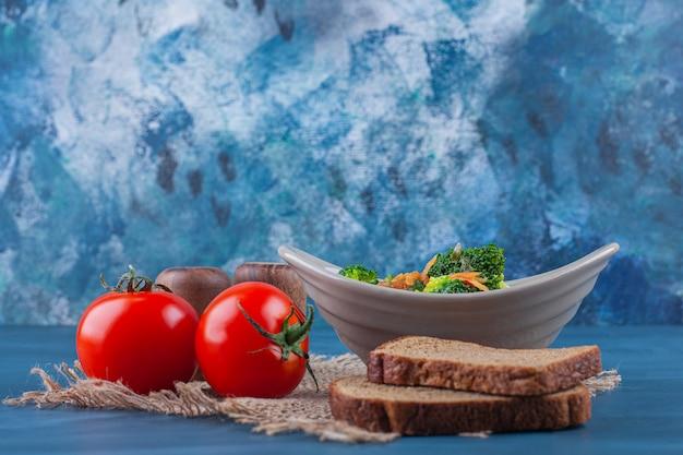 青いテーブルの上に、黄麻布のナプキンにチキンスープ、野菜、パンのボウル。