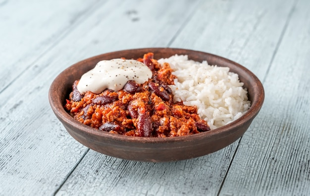 쌀과 사워 크림을 곁들인 칠리 콘 카르네 그릇