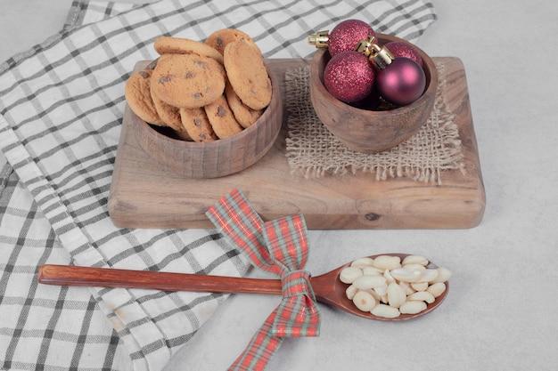 白いテーブルの上のチップクッキーとクリスマスボールのボウル。高品質の写真