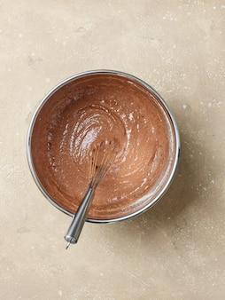 Чаша из теста для шоколадного торта на бежевом кухонном столе, вид сверху