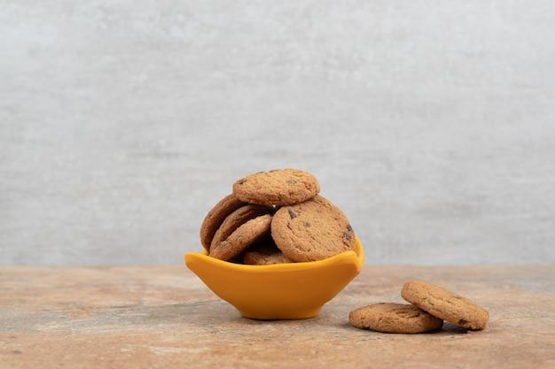 대리석 배경에 초콜릿 칩 쿠키의 그릇입니다.