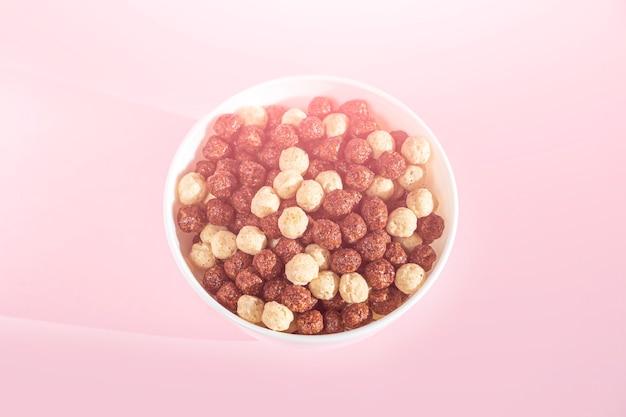 ピンクの背景にシリアルボールとチョコレートバニラ朝食のボウル。ヘルシーなドライクリスピーコーンボール。