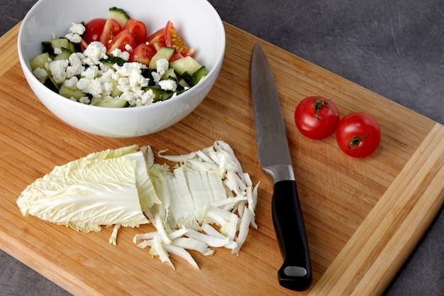 トマトとキュウリのみじん切りのボウルとまな板