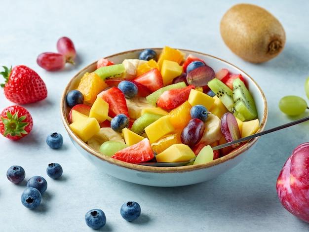 Чаша красочного салата из свежих фруктов на кухонном столе, выборочный фокус