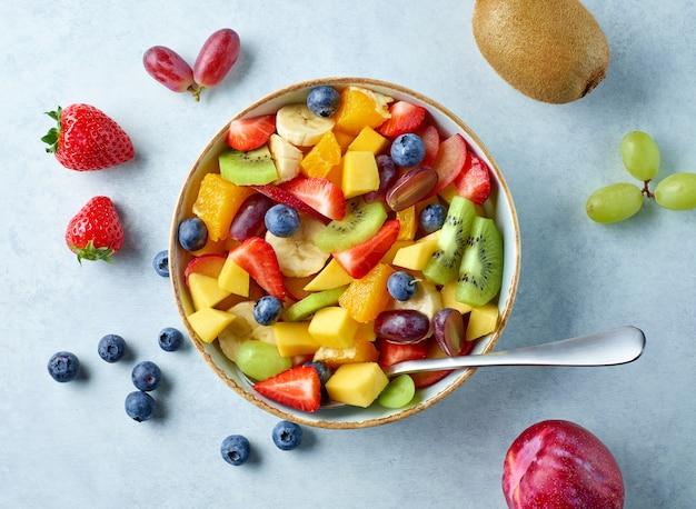 Чаша красочного салата из свежих фруктов на кухонном столе, вид сверху