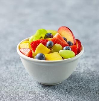 Чаша красочного салата из свежих фруктов на кухонном столе