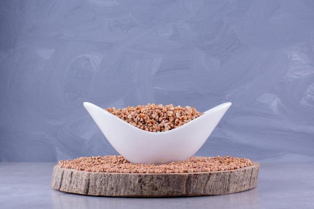 Чаша вареной гречки в середине кучи зерна гречихи на деревянной доске на мраморном фоне. фото высокого качества
