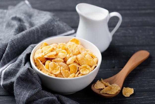 牛乳と木のスプーンで朝食のコーンフレークのボウル