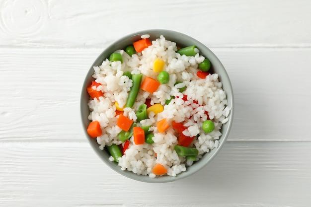 Чаша вкусный рис с овощами на деревянной поверхности