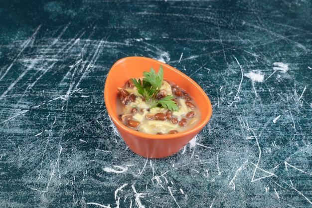 Чаша вкусного супа с макаронами и фасолью на синем фоне. фото высокого качества