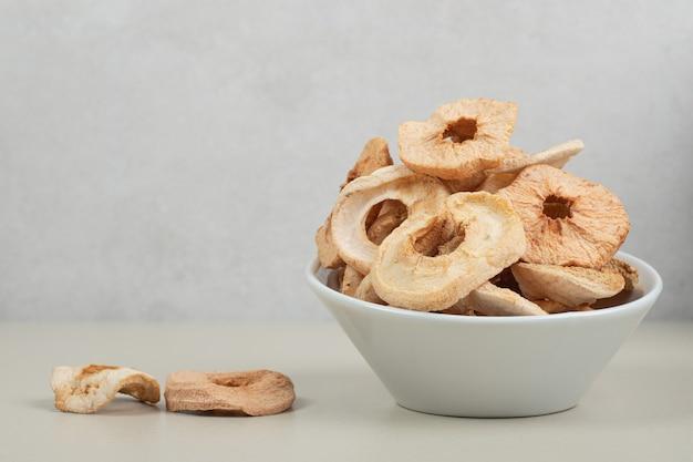 Чаша из сушеных яблочных колец на белой поверхности